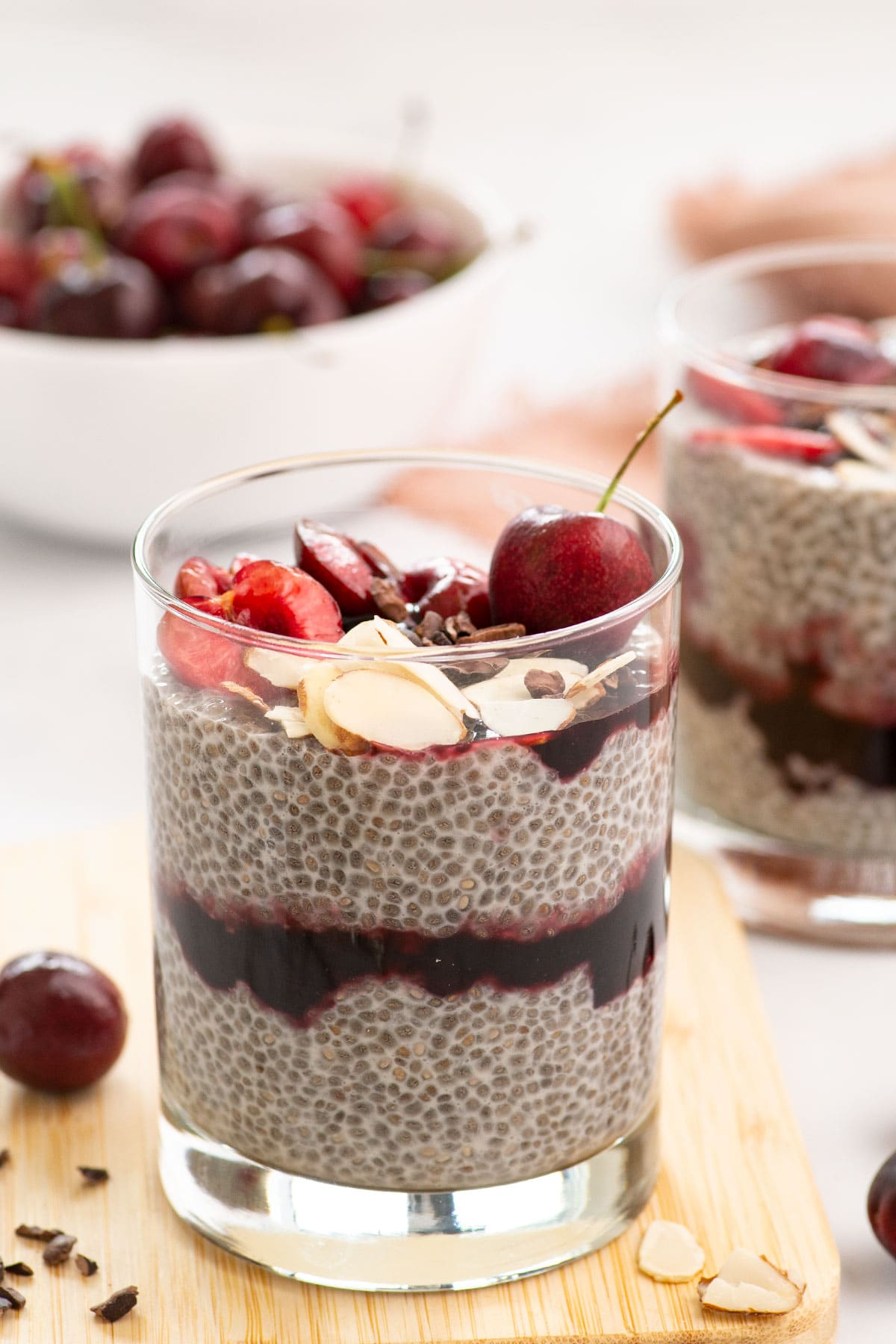 close view of layers of chia seed pudding and cherry compote with chocolate sauce and sliced almonds