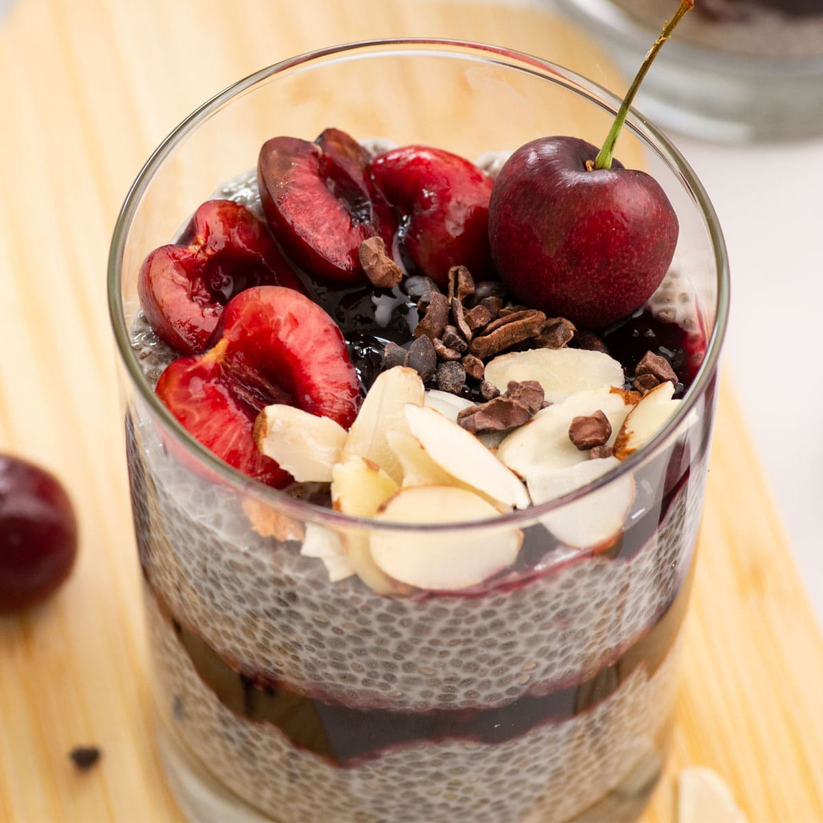 spoon drizzling chocolate over cherry chia pudding parfait on wooden board on light grey background with chocolate chips