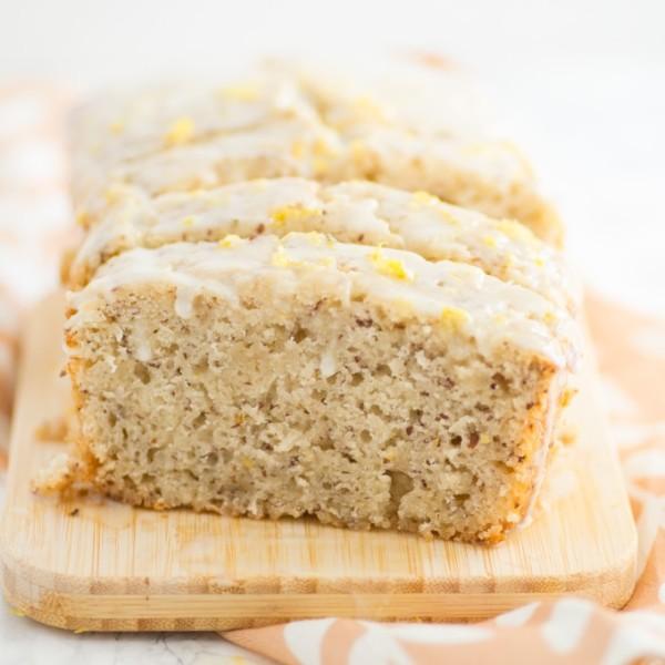 vegan lemon loaf on wood board with glaze