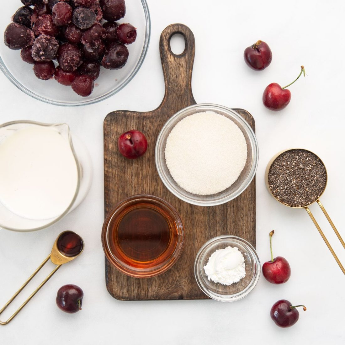 maple syrup, cherries, almond milk, vanilla extract, cane sugar, and chia seeds on wooden cutting board on white background