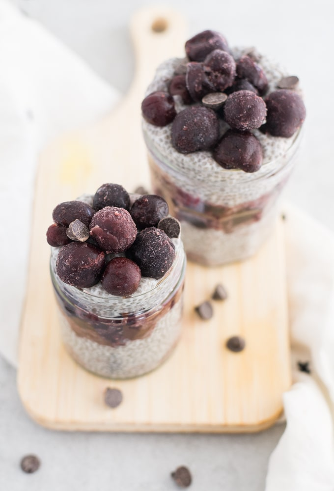 two chocolate cherry parfaits on wooden board with white napkin