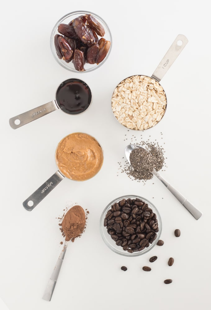 dates, oats, agave nectar, peanut butter, cocoa powder, chia seeds, and coffee beans on white background