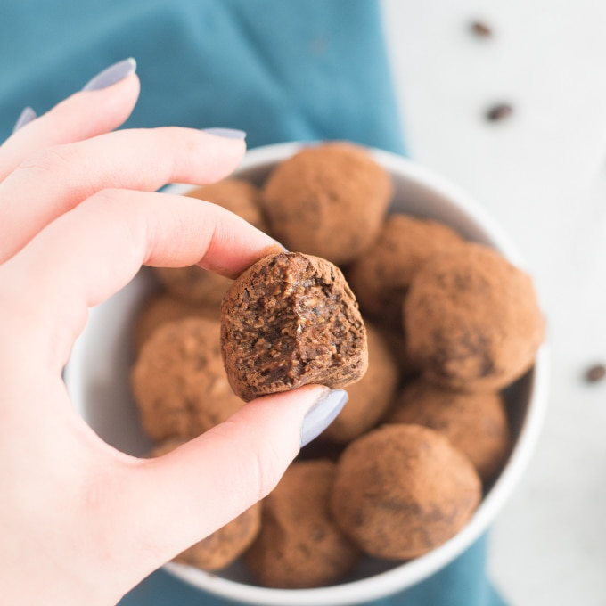 hand hold peanut butter chocolate energy bite over bowl