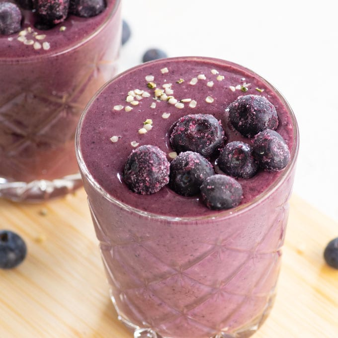 blueberry acai smoothie in glass topped with frozen blueberries and hemp seeds