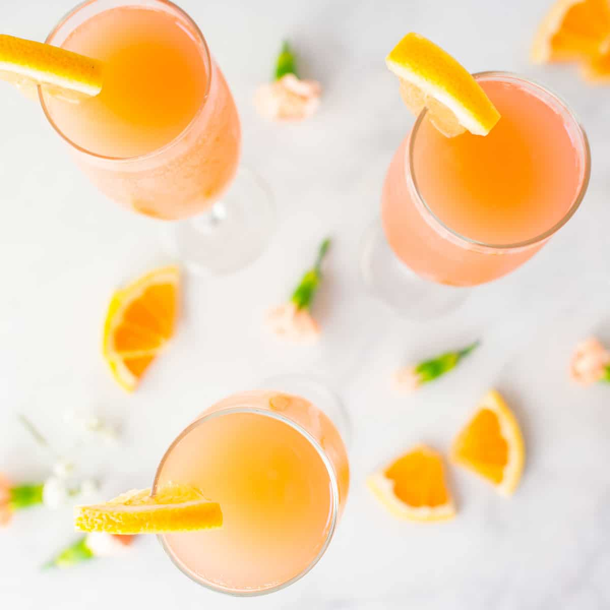 rose grapefruit mimosas with orange slices on marble background
