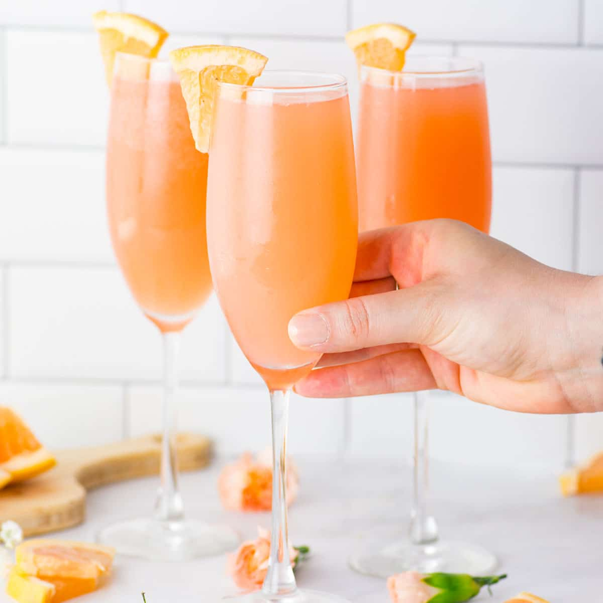 rose grapefruit mimosa with grapefruit slices on a marble counter