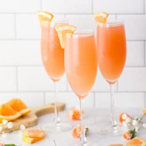 rose mimosa with grapefruit juice on marble counter with flowers