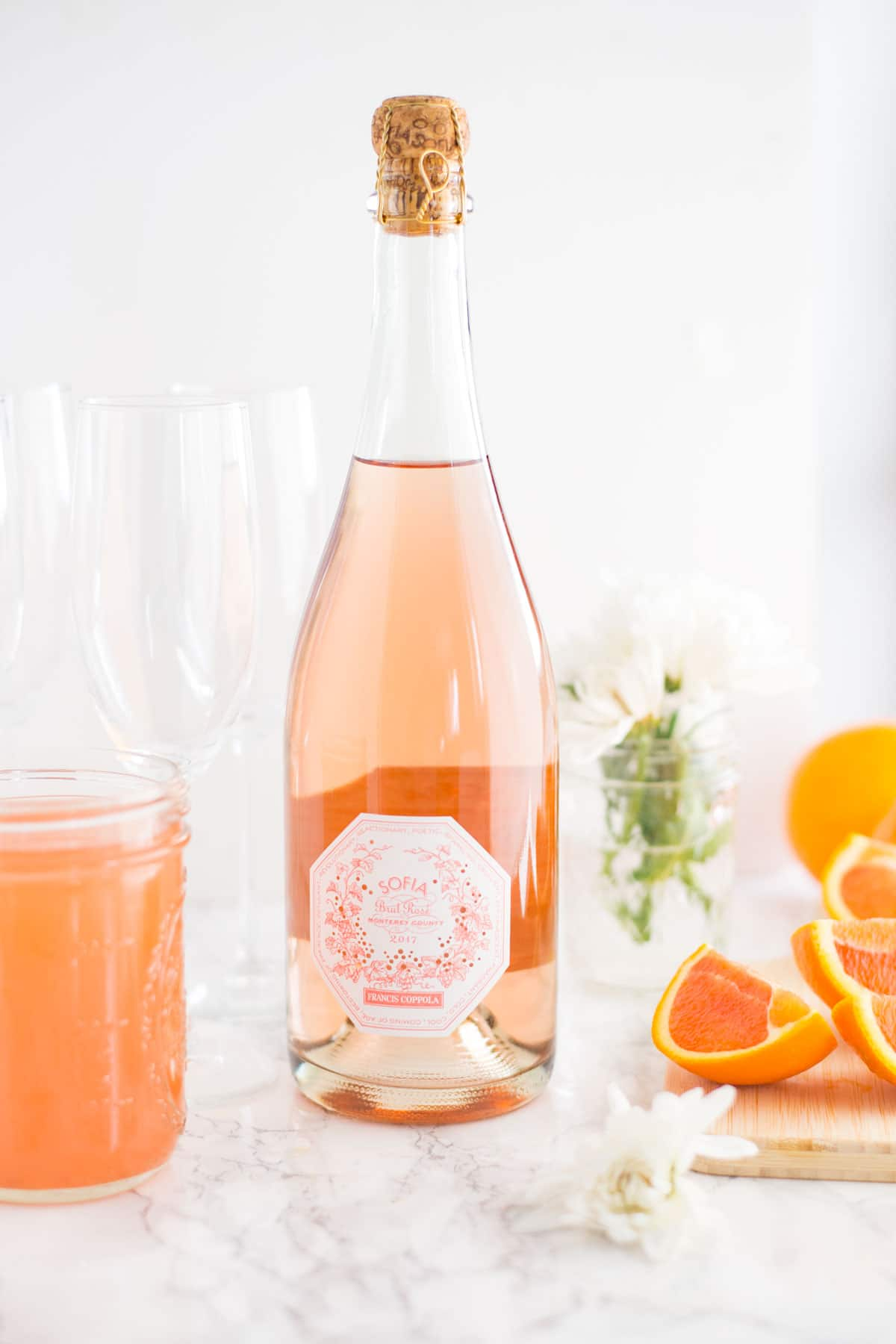rose champagne, orange slices, flowers, and grapefruit juice on marble background