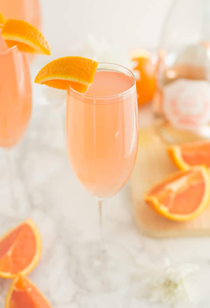 rose grapefruit mimosa with orange slices on a marble counter