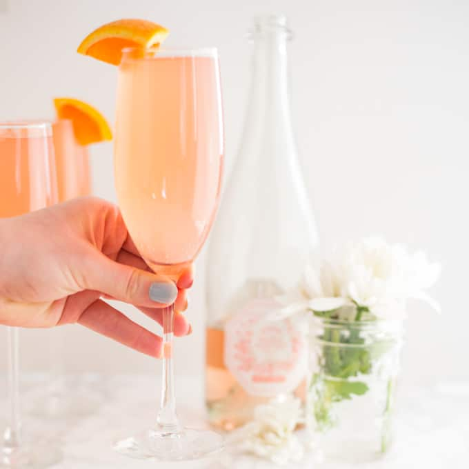 hand holding champagne flute of mimosa with champagne and flowers in background