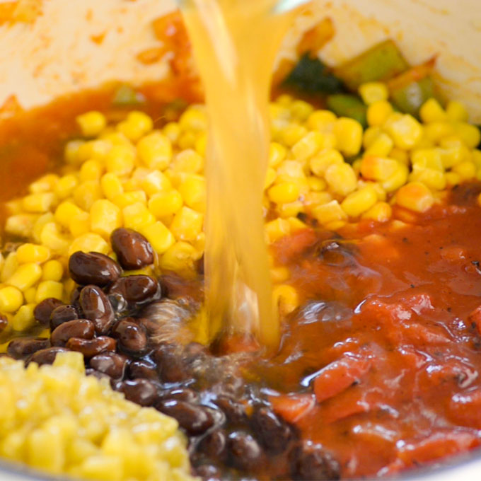 broth pouring into a soup pot with corn, black beans, and tomatoes