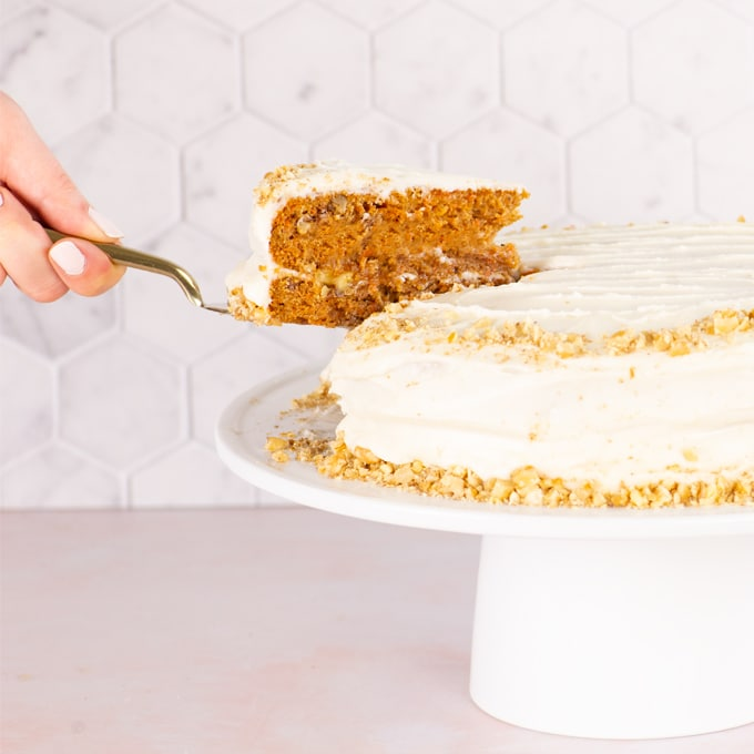 hand lifting slice of cake from cake stand