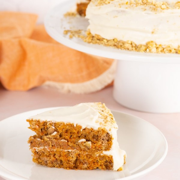 slice of vegan carrot cake with whole cake on a cake stand in the background
