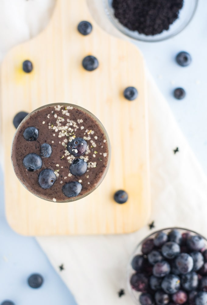 blueberry acai smoothie on wooden board with blueberries and white napkin
