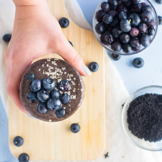 hand holding blueberry acai amoothie on wooden board with blueberries
