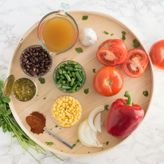 vegetable broth, tomatoes, garlic, bell pepper, onions, green beans, corn, black beans, chilis, spices, and cilantro on wood serving tray on marble counter