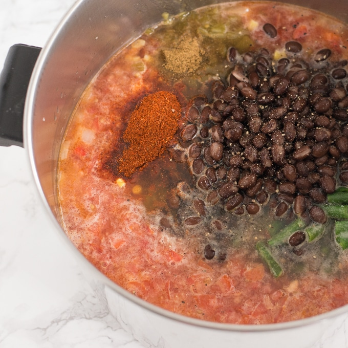stockpot with tomato broth, black beans, spices, and vegetables