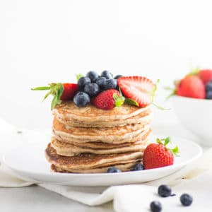 stack of vegan banana pancakes topped with blueberries and strawberries on white plate