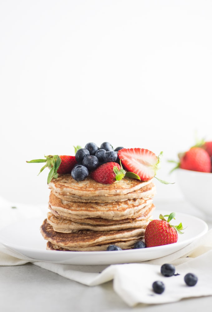 stack of vegan pancakes topped with blueberries and strawberries on white plate