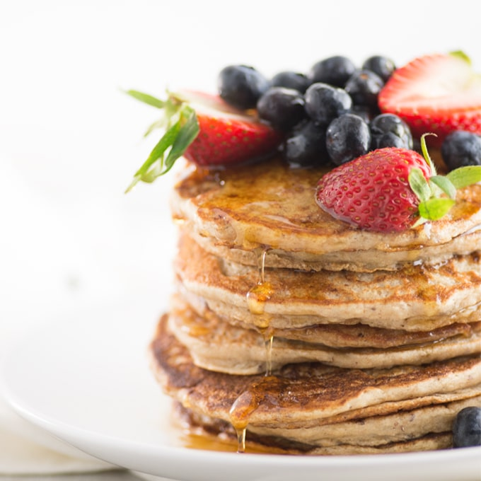 stack of pancakes topped with fresh fruit with maple syrup dripping off the sides