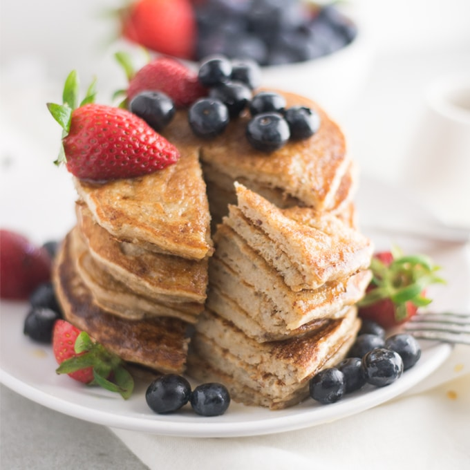 stack of vegan pancakes topped with fresh fruit on white plate