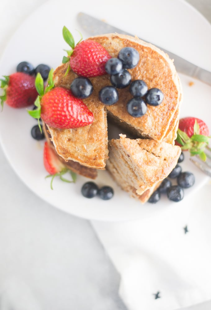 stack of vegan pancakes topped with fresh fruit on white plate on grey background