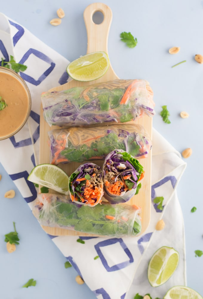 vegan spring rolls on wooden board on blue background with peanut sauce
