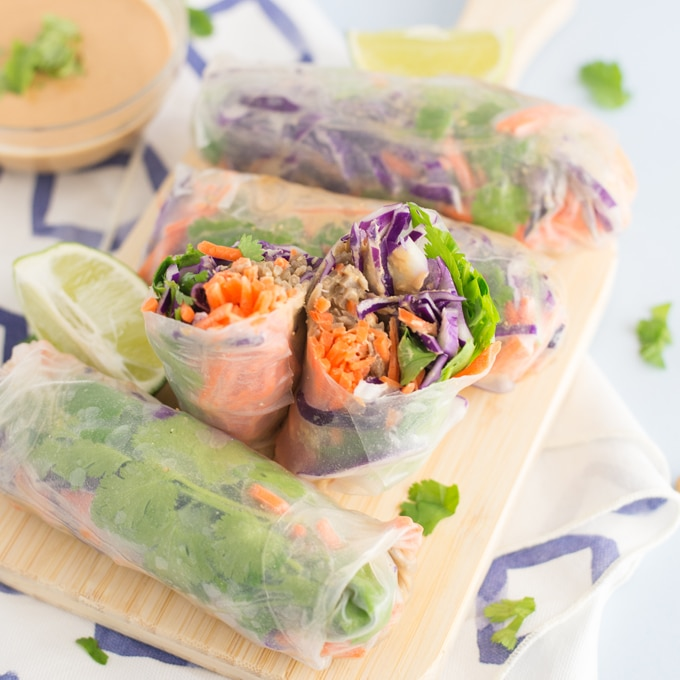 closeup of vegan spring rolls onn wood cutting board with peanut sauce