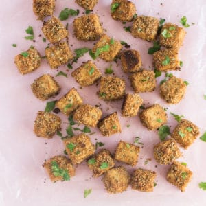 baked and breaded tofu bites on light pink background with parsley