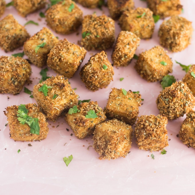 baked and breaded tofu bites on light pink background