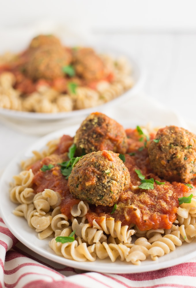 vegan meatballs with pasta and red sauce on white plate