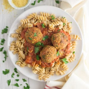 tofu vegan meatballs with pasta and sauce on white plate