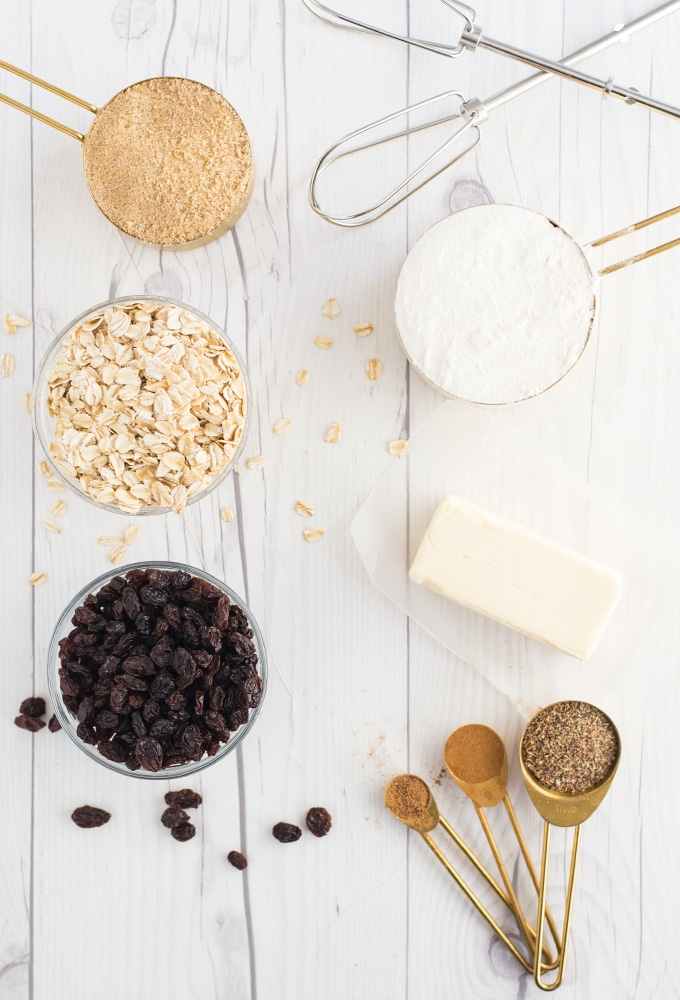 ingredients for vegan oatmeal raisin cookies on white wood background