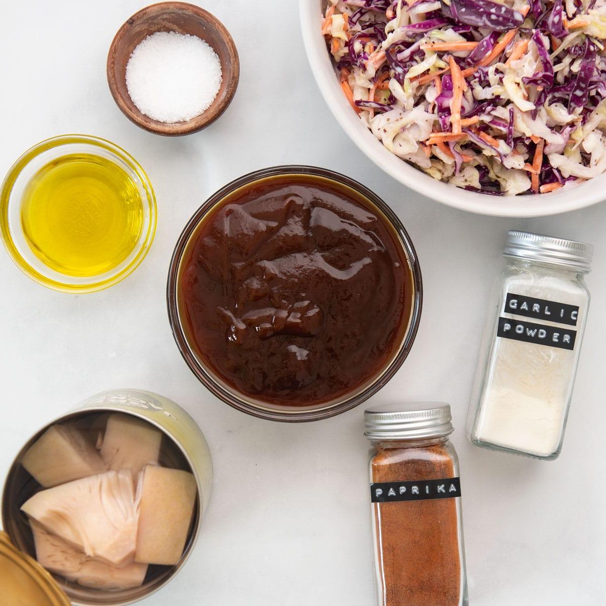 hamburger buns, bbq sauce, coleslaw, jackfruit, and seasonings on wooden board