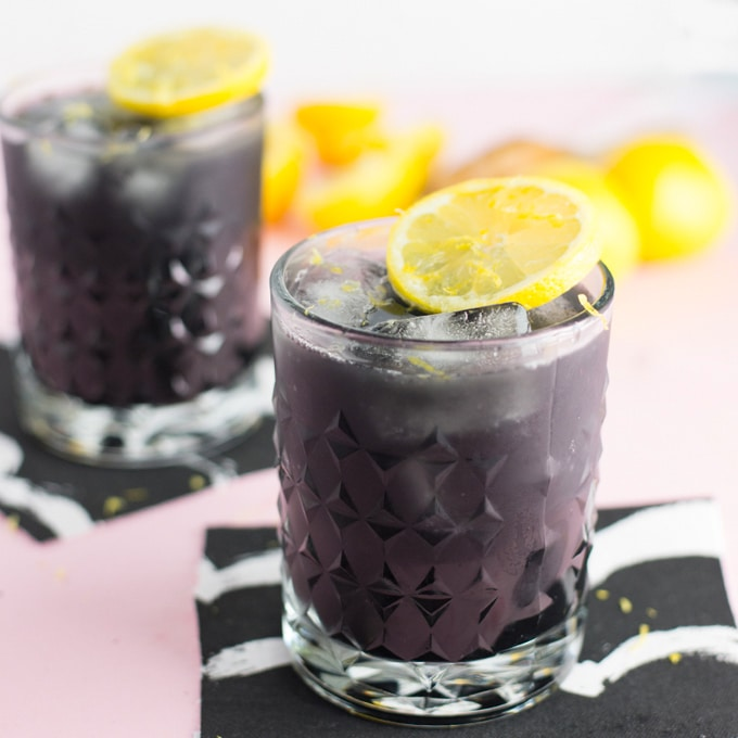 activated charcoal lemonade made with lemon juice, charcoal powder, and maple syrup. garnished with fresh lemons
