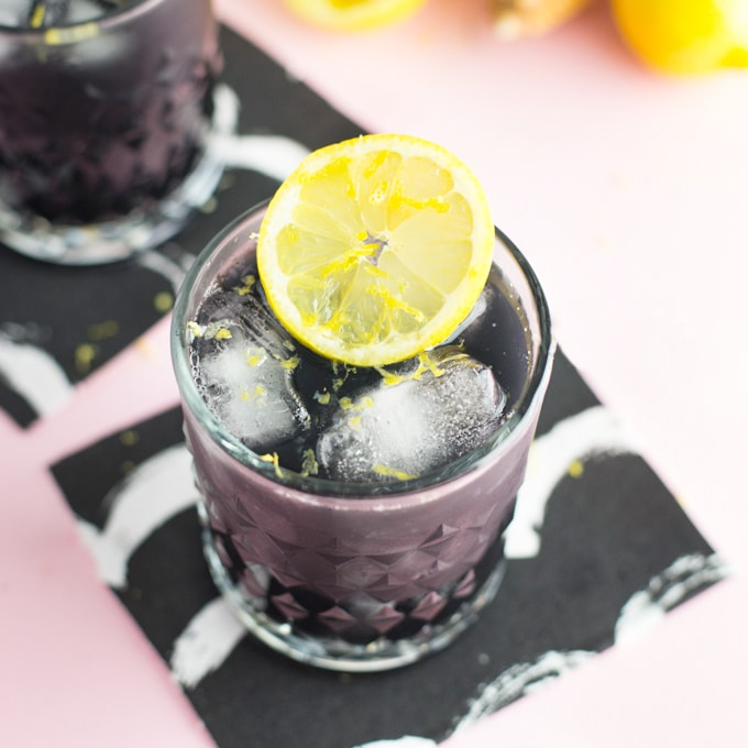 activated charcoal lemonade in glass with fresh lemon slice on pink background