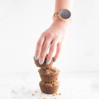 hand wearing jord wood watch grabbing vegan banana muffin on white background