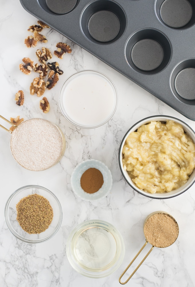 muffin tin, walnuts, almont milk, whole wheat flour, bananas, sugar, coconut oil, cinnamon, and flax seed on marble counter