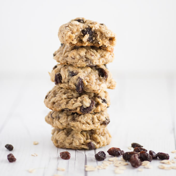 vegan oatmeal raisin cookies stacked on each other on white wood table