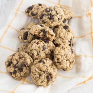 pile of vegan oatmeal raisin cookies on white and yellow kitchen towel