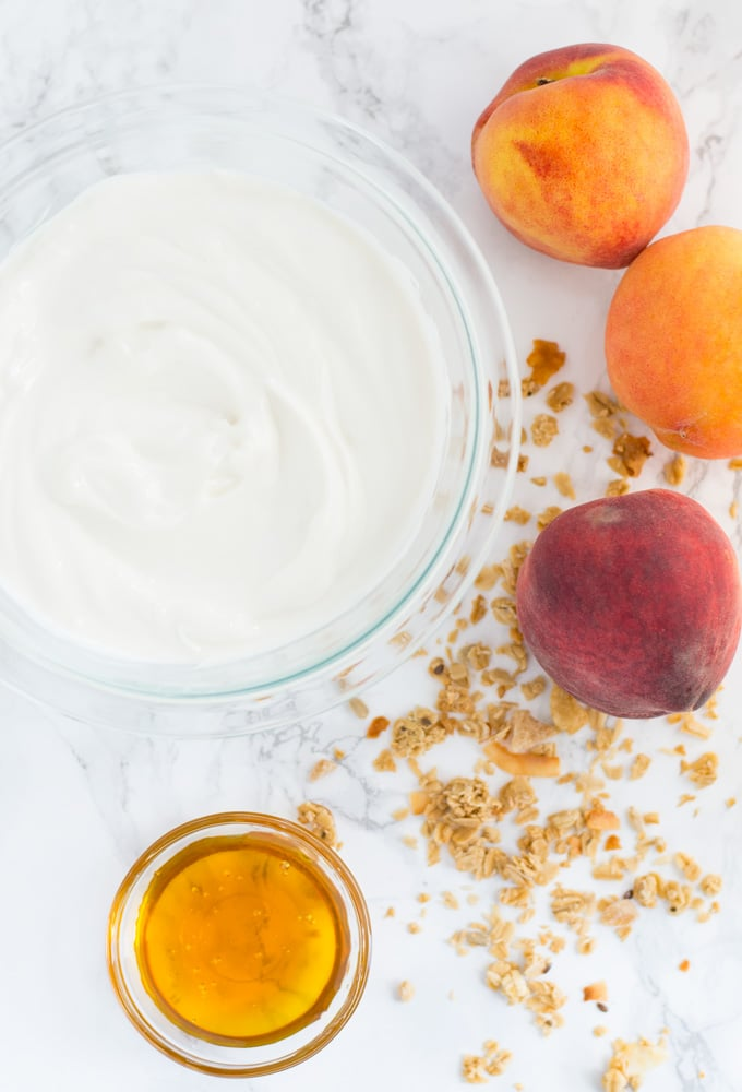 greek yogurt, honey, granola, and peaches on marble background