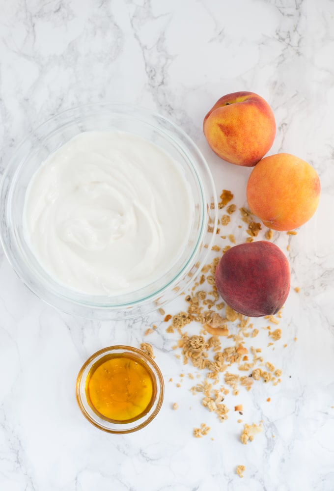 greek yogurt, honey, granola, and peaches on marble background