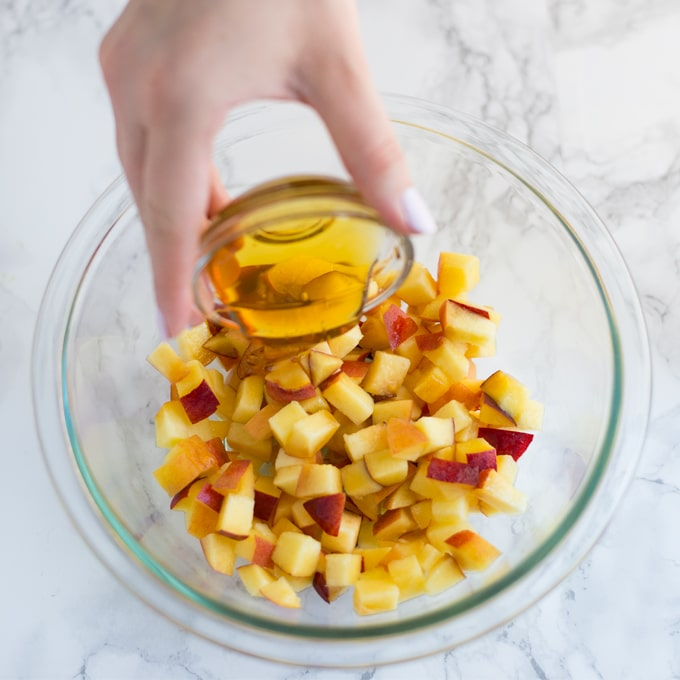 hand pouring honey into glass bowl full of diced peaches