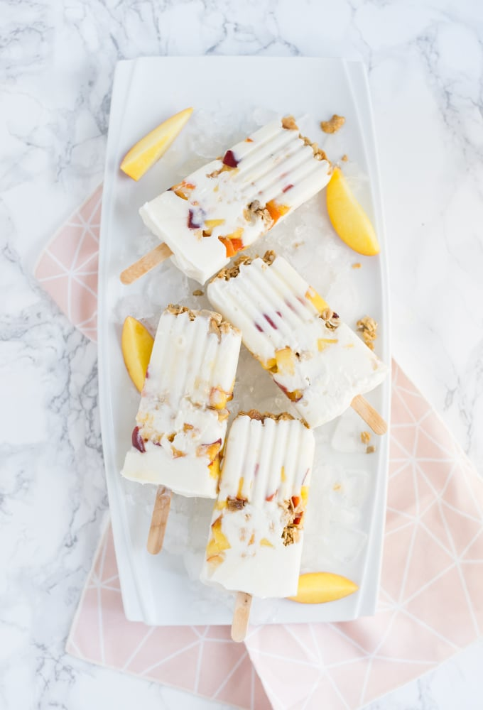 peaches and cream popsicles with peach slices on tray with pink napkin