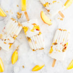 peach popsicles with greek yogurt and granola on marble background with ice and peach slices