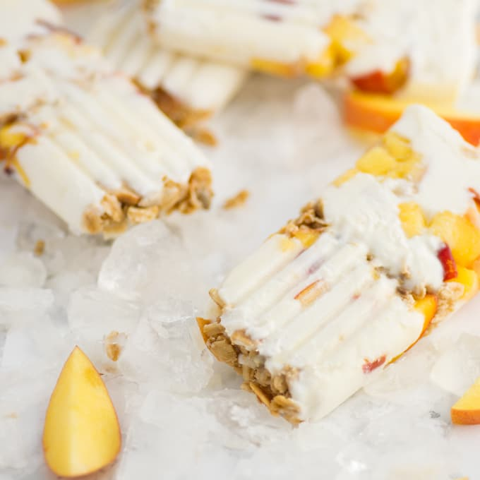 peach popsicles with greek yogurt and granola on marble background