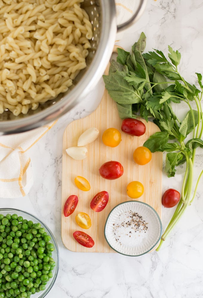 pasta, peas, garlic, tomatoes, basil, parsley, salt and pepper on marble background