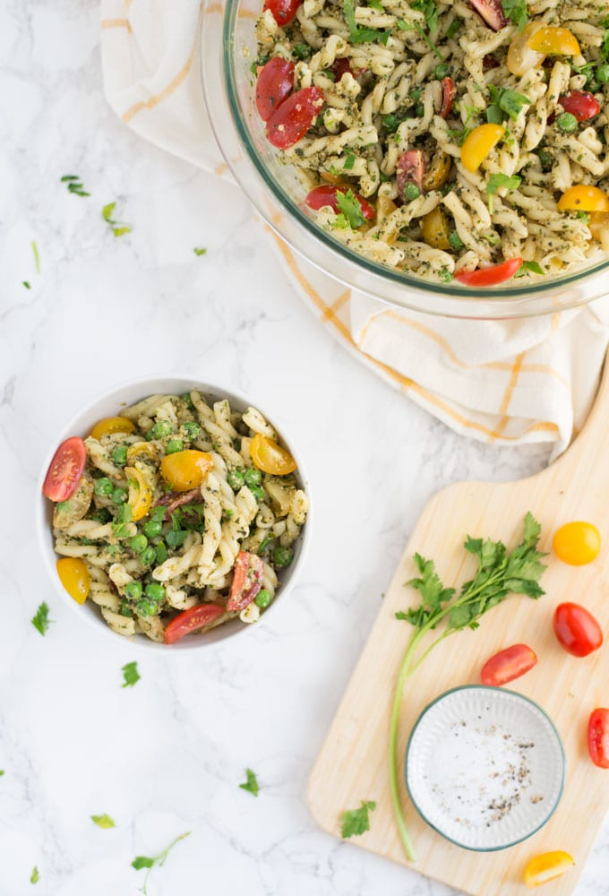 vegan pesto pasta salad in white bowl with wooden board, grape tomatoes, parsley, salt and pepper