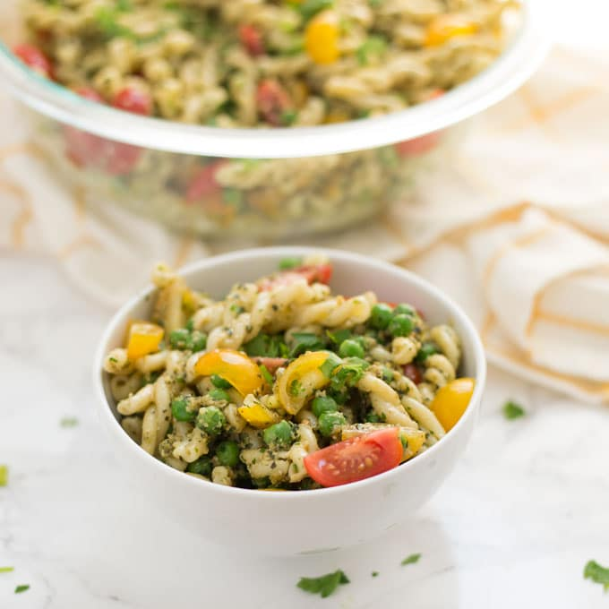 bowl of vegan pesto pasta salad with parsley on marble background