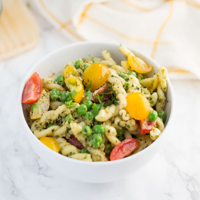 hand holding fork with vegan pesto pasta salad over bowl on marble background
